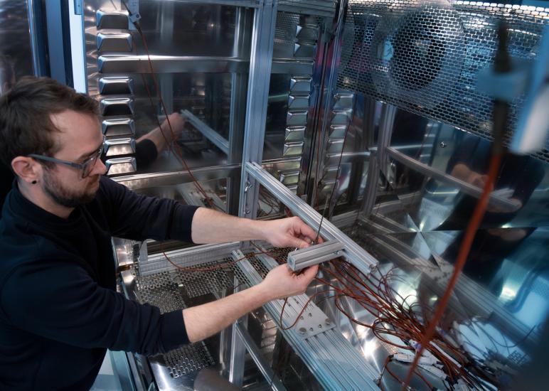 Geschäftsfeld Prüfzentrum - das Bild zeigt einen Testingenieur bei der Einrichtung des Klimaschranks