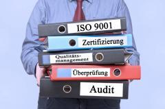 Mann mit Ordnern/Informationen der DIN EN  ISO Zertifizierung